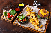 Take away burger menu on wooden tray at rusty background, top view. Black bun cheeseburger with baked potato wedges and sauces set, fast food concept