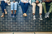 Cropped shot of a group of students sitting on a wall on campus