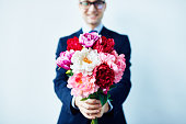 Elegant man giving a beautiful bouquet of red and white flowers