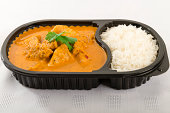 Takeaway Curry - Chicken curry with coconut milk and plain rice in a plastic container on a white background.