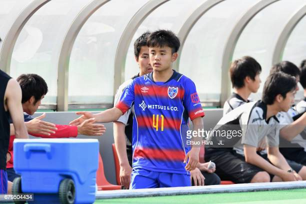 Takefusa Kubo of FC Tokyo high fives with his team mates after being substituted during the JLeague J3 match between FC Tokyo U23 and FC Ryukyu at...