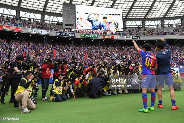 Takefusa Kubo of FC Tokyo is photographed by media photographers as he celebrates his side's 10 victory with Kensuke Nagai at his top team debut game...