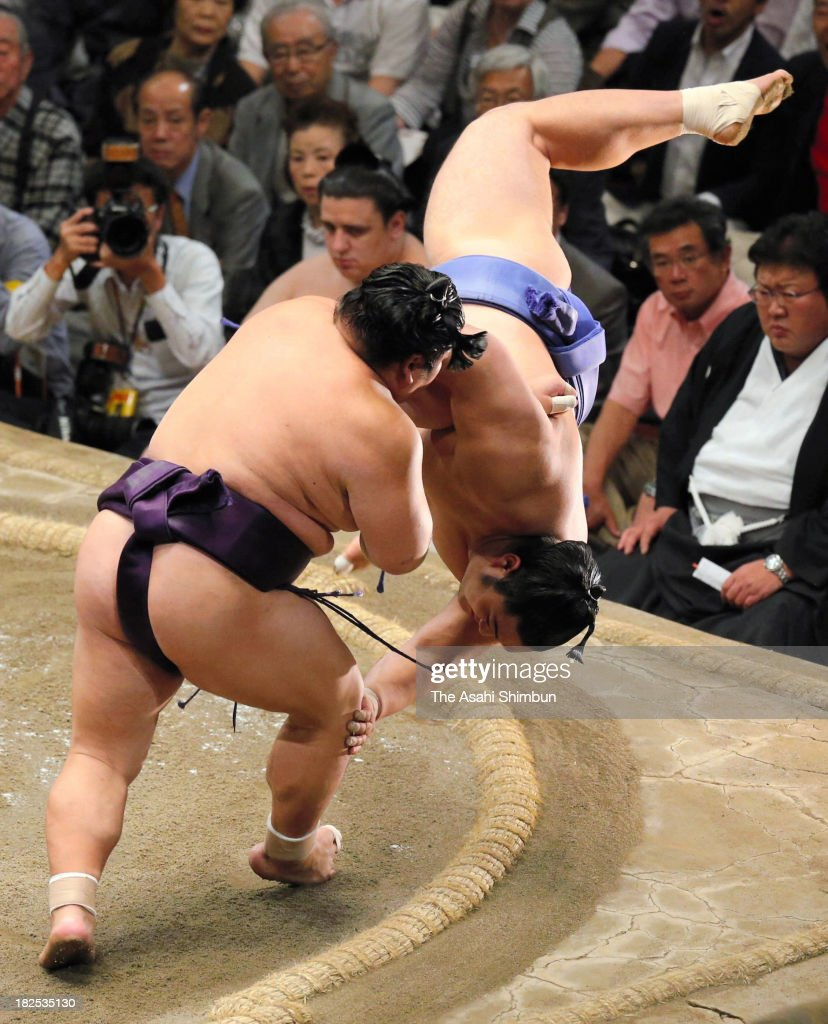 Takekaze (L) throws Okinoumi to win during day fifteen of the Grand Sumo Autumn Tournament at Ryogoku Kokugikan on September 28, 2013 in Tokyo, Japan.