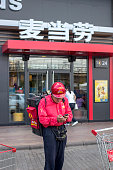 A takeout deliveryman is checking message on his mobile phone outside a McDonald's restaurant McDonalds is to begin piloting a mobile ordering and...
