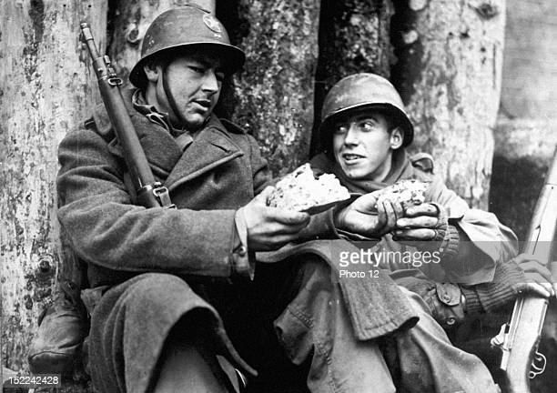 G I takes a piece of bread offered to him by a French 'Poilu' of the 1st French Army in Rouffach on the fifth of Feb as French and American forces...
