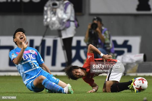 Takeshi Aoki of Sagan Tosu and Yoshiaki Komai of Urawa Red Diamonds compete for the ball during the JLeague J1 match between Sagan Tosu and Urawa Red...