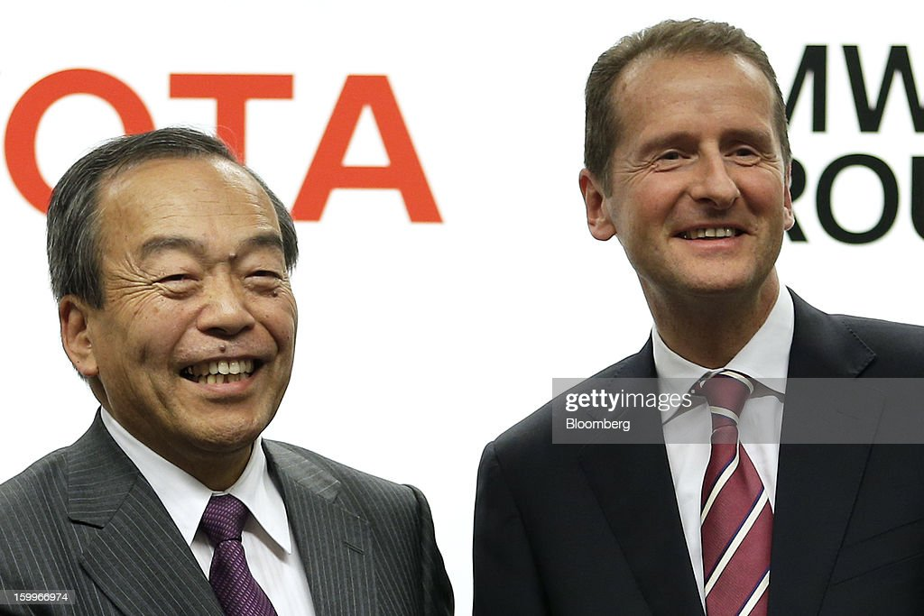 Takeshi Uchiyamada, vice chairman of Toyota Motor Corp., left, and Herbert Diess, development chief of Bayerische Motoren Werke AG (BMW), react during a photo session at a joint news conference in Nagoya, Aichi Prefecture, Japan, on Thursday, Jan. 24, 2013. Toyota, the world's biggest maker of gasoline-electric hybrid vehicles, signed a binding agreement with BMW to jointly develop fuel-cell systems for cars. Photographer: Kiyoshi Ota/Bloomberg via Getty Images Photographer: Kiyoshi Ota/Bloomberg via Getty Images