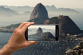 Man taking a photo with cellphone showing only the hand. It's a Sugarloaf Mountain in Rio de Janeiro, Brazil. It is a misty morning.