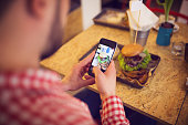 A photo of young man taking a picture of his lunch by his mobile phone.