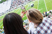 2 young women spectators taking a picture at sports event with a smart phone.