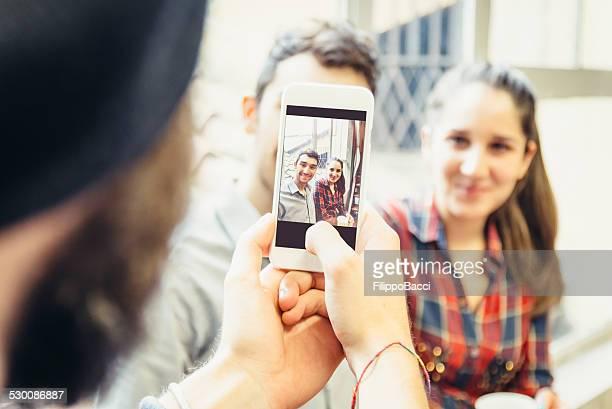 Nimmt ein Bild von zwei Freunde mit Smartphone