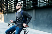 Shot of a businessman using his cellphone while going to work with his bicycle.