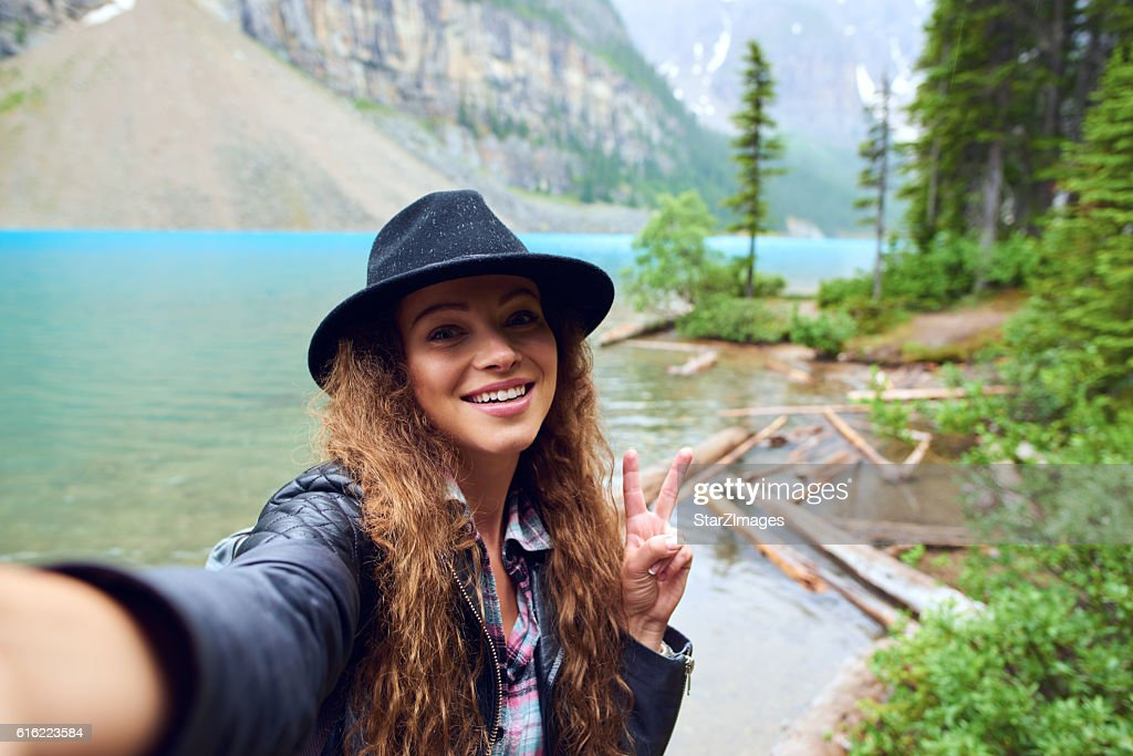 Taking a selfie over the lake and mountain view : Stock Photo