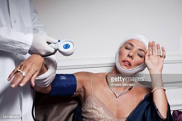 Taking blood pressure of a post-op senior woman
