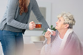 Young woman taking care of ill grandmother bringing her a cup of lemon tea as a cure for common cold and flu