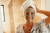 Attractive young woman standing in the bathroom with a facial mask