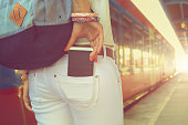Taking cellphone from/to the pocket with de-focused city tram / train.