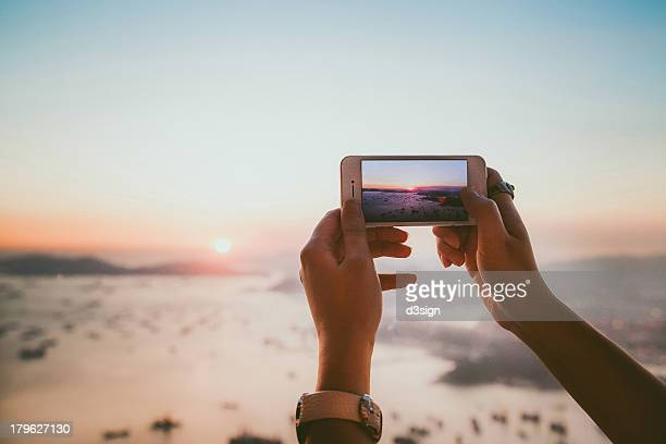Taking photo of beautiful sunset with smartphone