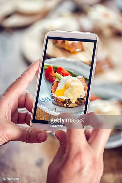 Taking Photo with Smartphoen of Egg Benedict For Breakfast