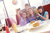 Group of teens taking selfie on smart phone in fast food restaurant