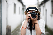 Asian girl who loves photography is travelling in an old town in South China with her camera.