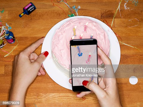 Taking picture with phone of cake with candles