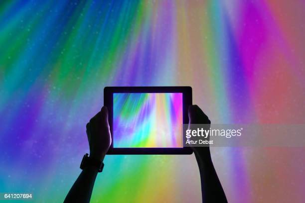 Taking pictures from personal perspective with tablet of the beautiful colorful northern lights falling from the sky in Iceland in a stunning clear and nice lights with the sky full of stars. Aurora borealis.