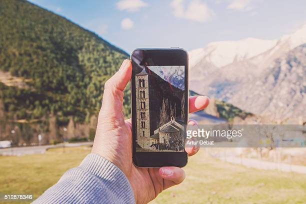 Taking pictures with smartphone of the Vall de Boi romanesque architecture with tall church and beautiful landscape in the Catalan Pyrenees.