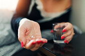 Close up of hand female taking sleeping pills and a glass of water
