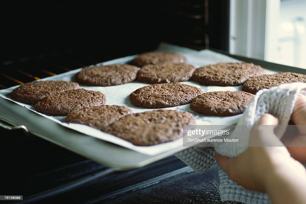 Taking sheet of cookies out of the oven