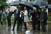 Taking shelter from the pouring rain under umbrellas US President Barack Obama his daughter Malia and members of the first family take a walking tour...