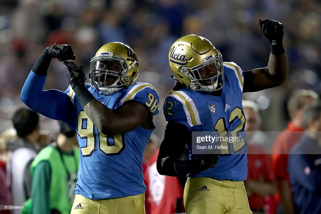 Takkarist McKinley #98 and Jayon Brown #12 of the UCLA Bruins react to a tackle during the second half of a game against the Arizona Wildcats at the Rose Bowl on October 1, 2016 in Pasadena, California.