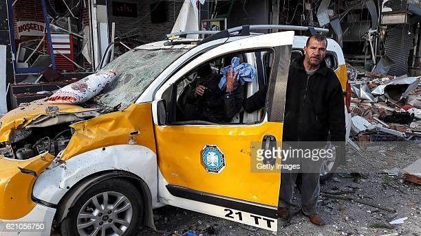 A taksi driver is seen at the blast site as damage caused by an explosion on November 4 2016 in Diyarbakir Turkey Eight people were killed including...
