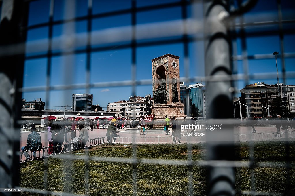 Taksim monument is pictured through a fence set as part of the security measures for May day, April 30, 2016 at the Taksim square in Istanbul. Istanbul braced for a major security lockdown for May Day on Sunday, with almost 25,000 police on duty and numerous roads closed for an occasion that regularly sees clashes between Turkish protesters and police. / AFP / OZAN