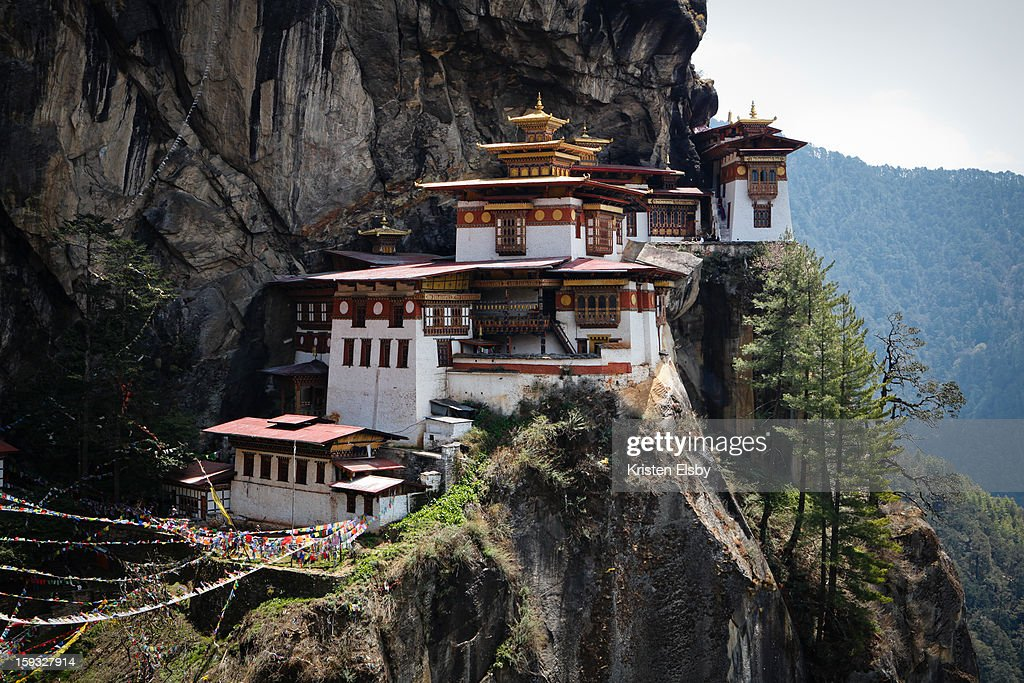 CONTENT] Taktsang Palphug Monastery, also known as Tiger's Nest, sits on a sheer cliff face 900m above Paro Valley, requiring a strenuous climb for several hours to reach the complex. Its location has been considered a sacred site for over 1,000 years and nearly 400 years ago, the original monastery and temple complex was built here. Unfortunately it was mostly destroyed in a fire in 1998 and the present architecture, aside from several temples that were not damaged at that time, is almost entirely a reconstruction. From this vantage point, there are still another 350 steps remaining - down the steep cliff face bedecked in prayer flags, across a small bridge over a waterfall, and up more steps - before reaching the monastery itself.