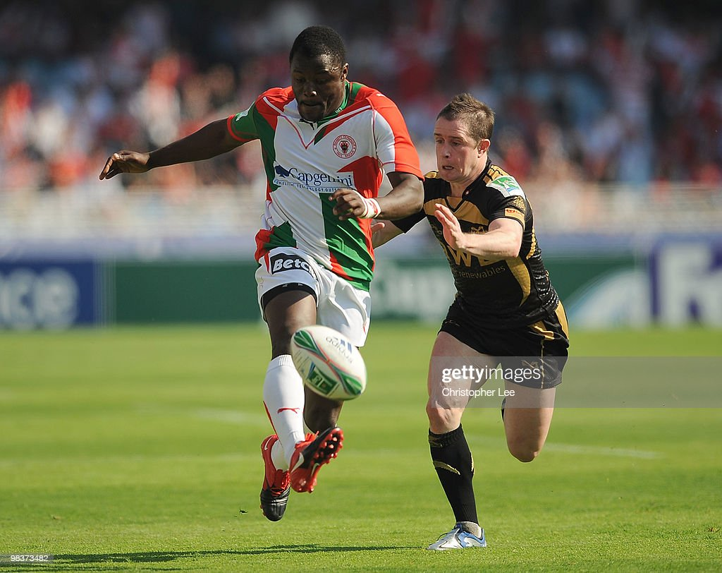 Takudzwa Ngwenya of Biarritz kicks the ball as Shane Williams of Ospreys comes in to tackle during the Heineken Cup Quarter Final match between...