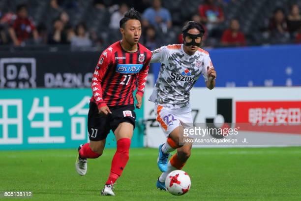 Takuma Arano of Consadole Sapporo controls the ball under pressure of Takuma Edamura of Shimizu SPulse during the JLeague J1 match between Consadole...