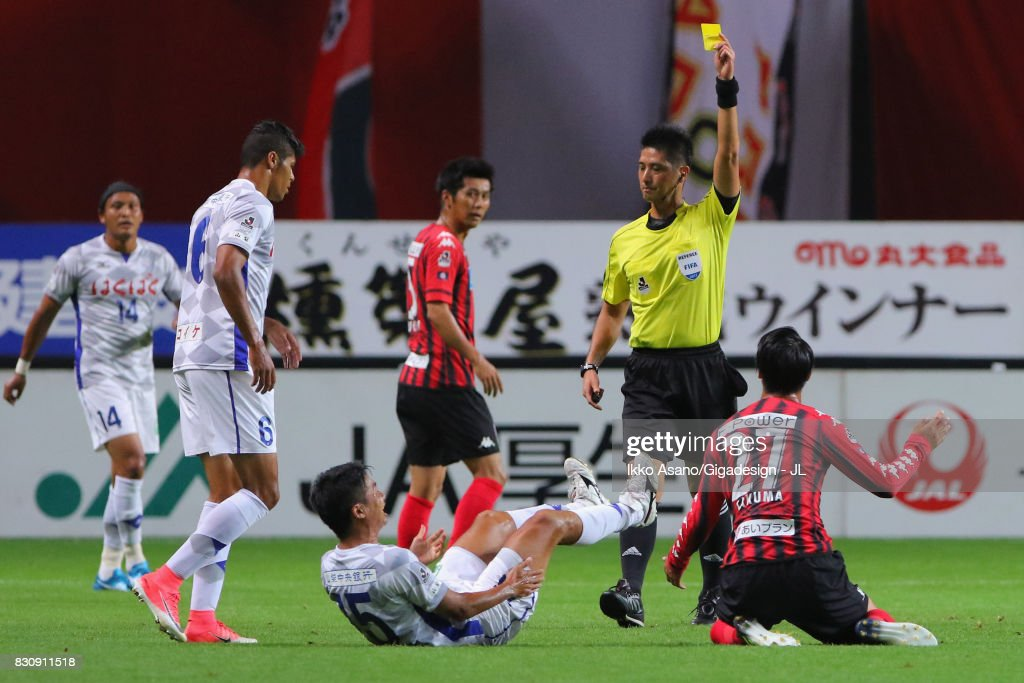 Takuma Arano (1st R) of Consadole Sapporo is shown a yellow card by referee Yudai Yamamoto (2nd R) during the J.League J1 match between Consadole Sapporo and Ventforet Kofu at Sapporo Dome on August 13, 2017 in Sapporo, Hokkaido, Japan.