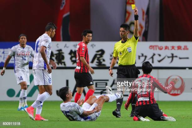 Takuma Arano of Consadole Sapporo is shown a yellow card by referee Yudai Yamamoto during the JLeague J1 match between Consadole Sapporo and...