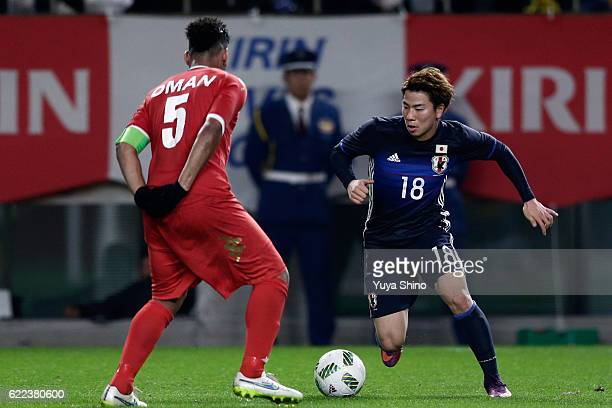 Takuma Asano of Japan and Nadir Awadh Bait Mabrook of Oman compete for the ball during the international friendly match between Japan and Oman at...