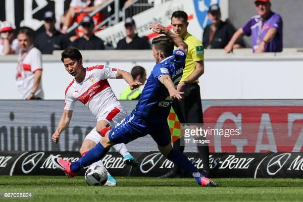 Takuma Asano of Stuttgart and Dennis Kempe of Karlsruher SC battle for the ball during the Second Bundesliga match between VfB Stuttgart and...