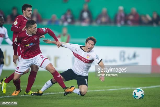 Takuma Asano of Stuttgart is fouled by Joel Abu Hanna of Kaiserslautern during the DFB Cup match between 1 FC Kaiserslautern and VfB Stuttgart at...