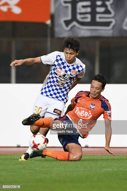 Takuma Nishimura of Vegalta Sendai is tackled by Ryota Isomura of Albirex Niigata during the JLeague J1 match between Albirex Niigata and Vegalta...