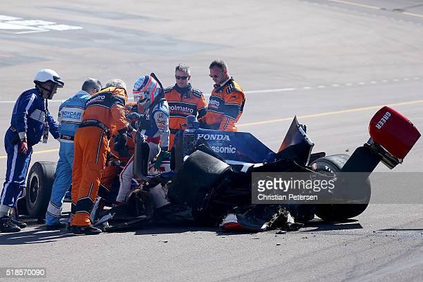 Takuma Sato of Japan driver of the ABC Supply Foyt Enterprises Honda is helped oiff the track by safety crew after a wreck during practice for the...