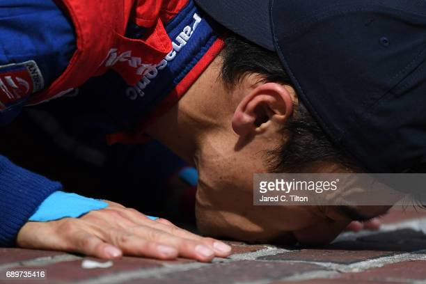 Takuma Sato of Japan driver of the Andretti Autosport Honda celebrates by kissing the bricks after winning the 101st Indianapolis 500 at Indianapolis...