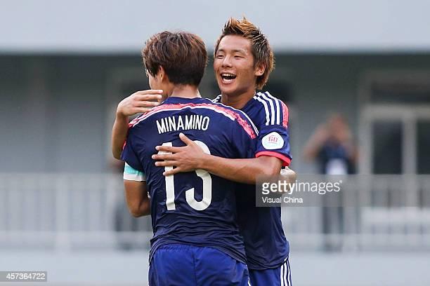 Takumi Minamino of Japan celebrates with team mate Yosuke Ideguchi after scoring the equalizing goal with a penalty during the AFC U19 Championship...