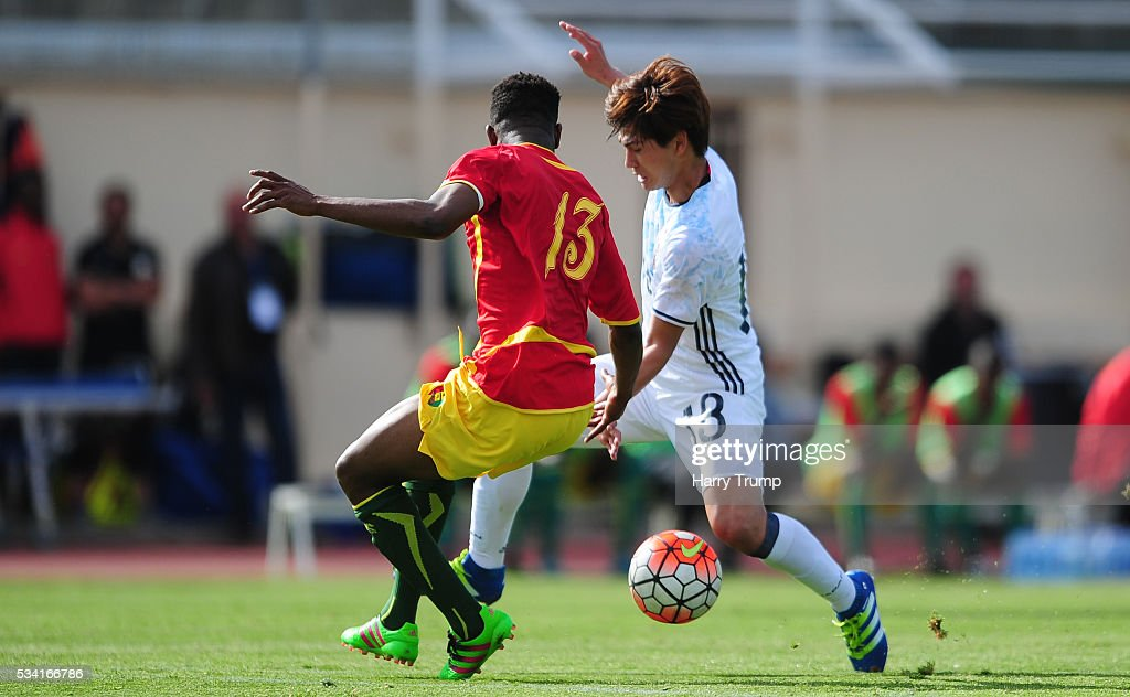 Takumi Minamino of Japan is tackled by Abdoulaye Cisse of Guinea during the Toulon Tournament match between Guinea and Japan at Stade Antoinr Baptiste on May 25, 2016 in Six-Fours-Les-Plages, France.