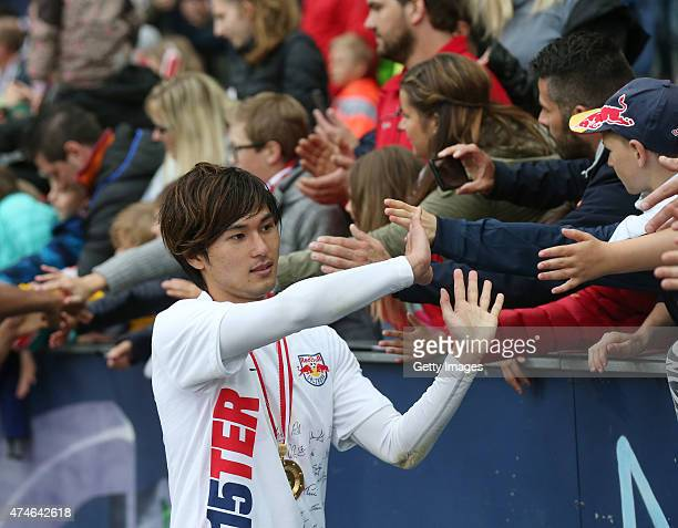 Takumi Minamino of Salzburg celebrates with the fans after winning the Austrian Soccer Championship after the tipico Bundesliga match between RB...