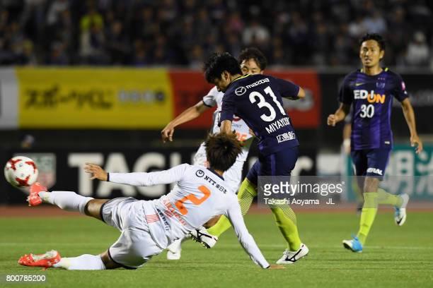 Takumi Miyayoshi of Sanfrecce Hiroshima shoots at goal while Kosuke Kikuchi of Omiya Ardija tries to block during the JLeague J1 match between...