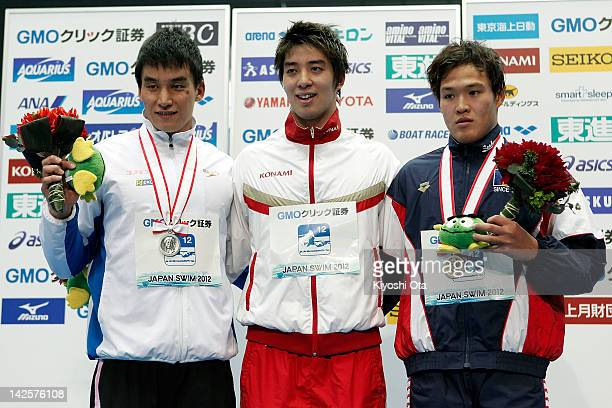 Takuro Fujii celebrates after winning the Men's 100m Butterfly final with Takeshi Matsuda and Hirofumi Ikebata at an award ceremony during day seven...